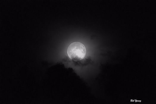 Shot at:  I had to change it from a color photo to black and white to bring out the moon's surface. It was cloudy and you can see some of the clouds and the haze.